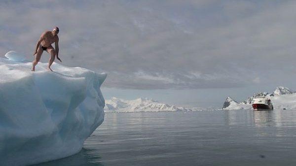 Lewis Pugh skacze do wody z góry lodowej.